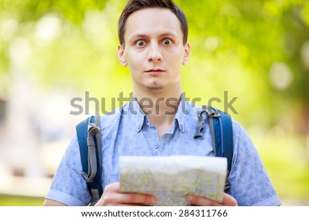 Lost tourist holding map in hands and looking at camera  - stock photo