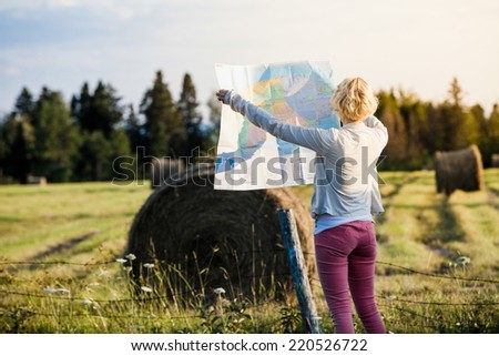 Lost Young Woman on a Rural Scene Looking at a Map - stock photo