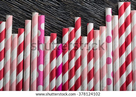 Lot of colorful straws lying on a dark textured surface. Straws are red and white, pink and white, purple and white. There is free space above the straws. Close-up photo. Horizontal. - stock photo