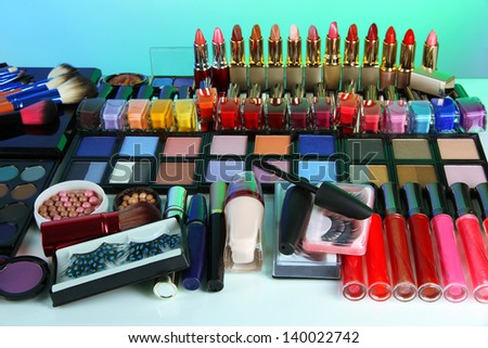 Lot of different cosmetics on blue background - stock photo