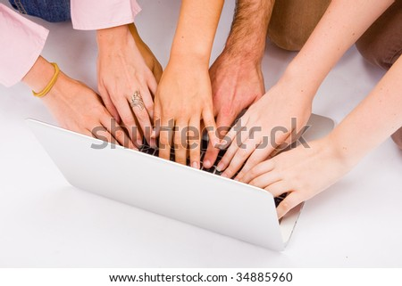 Lot of hands with grey laptop computer on desk - stock photo
