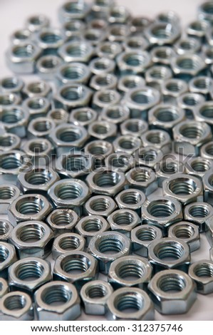 Lot of metal nuts arranged as the background for advertising. - stock photo