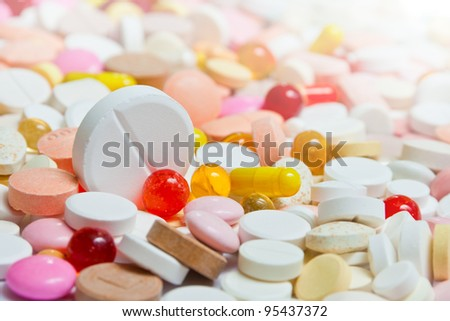 Lot of pills with big among them. Focus on big pill. - stock photo