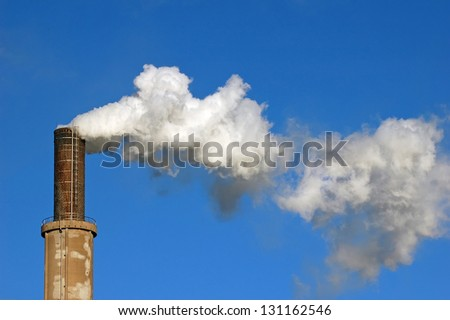 lot of smoke from chimney at winter morning in nature