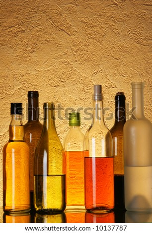 Lots bottles of alcoholic beverages over textured background - stock photo