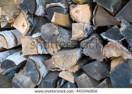 Lots of aged stacked chopped firewood in background texture.