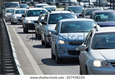 Lots of cars standing in the queue at roadway - stock photo