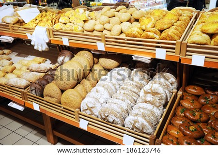 lots of fresh crisp loaves of bread on shelves in store; abundance of delicious soft bread - stock photo