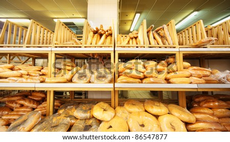 lots of fresh crisp loaves of bread on shelves in store; bread is one of main food - stock photo