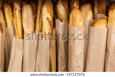 Lots of fresh crisp loaves of bread on shelves in supermarket.