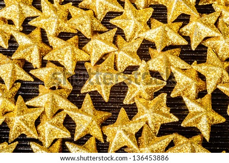 Lots of golden sparkling five pointed stars on black glass. These are glittering with shiny golden color. - stock photo