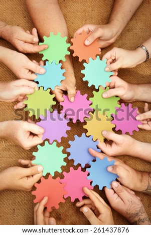 lots of hands holding brightly coloured cogs - stock photo