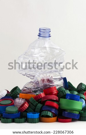 lots of plastic caps with a plastic crushed bottle isolated on white background  - stock photo