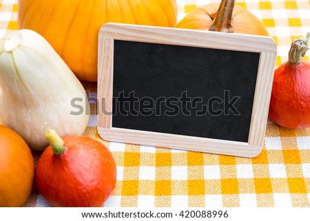Lots of Pumpkins and Slate with Copyspace on a yellow checkered tablecloth - stock photo