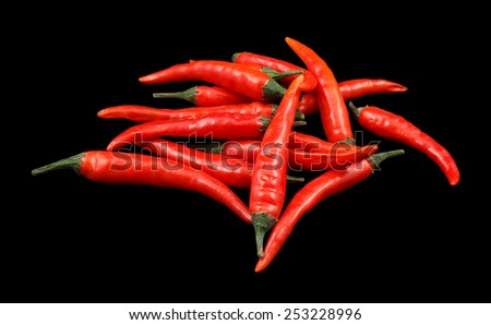 Lots of red chili peppers isolated on black  - stock photo