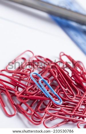 lots of red paperclips with a blue one  - stock photo