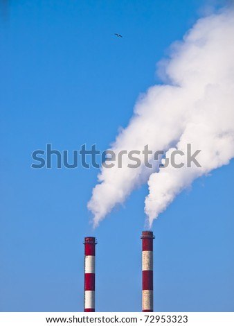 Lots of smoking chimneys other blue sky - stock photo