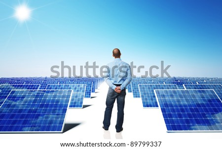 lots of solar panel and blue sky with man back view - stock photo