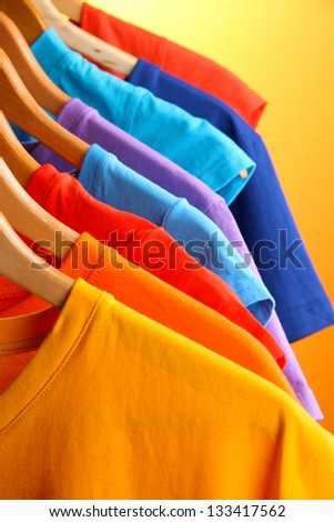 Lots of T-shirts on hangers on orange background