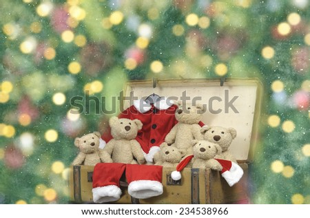 lots of teddy bears and santa outfit in an old vintage suitcase, christmas lights in background - stock photo