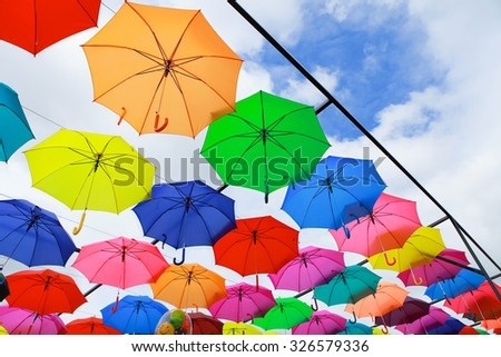 Lots of umbrellas coloring the sky in the city of Pai, Thailand with selective focus - stock photo