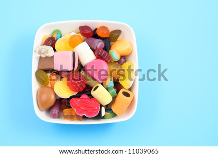 lots of various jelly beans in bowl blue background