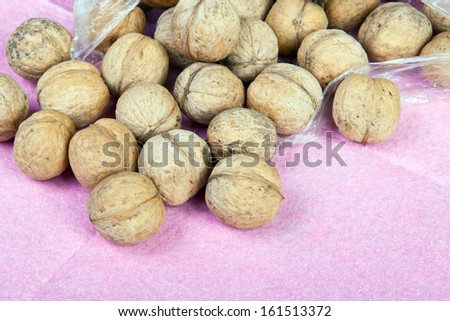 lots of walnuts on a purple background - stock photo