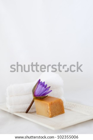 Lotus flower, natural soap and towels on marble tray at a spa - stock photo