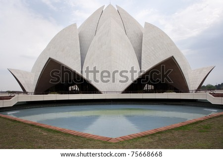 Lotus shaped top of the Baha'i temple reflected in one pool.