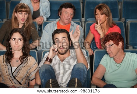 Loud bearded man on phone annoys the audience in theater - stock photo