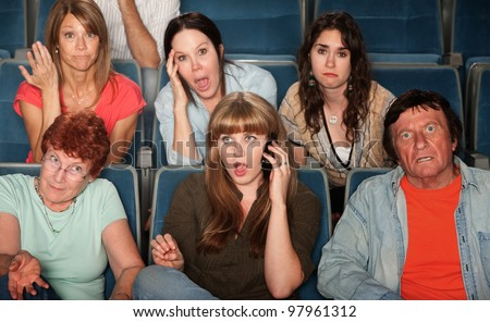 Loud woman on phone annoys audience in theater - stock photo