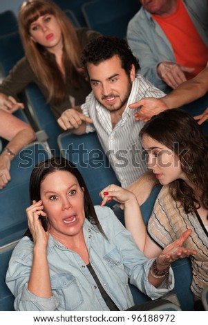 Loud woman on phone frustrates audience in theater - stock photo