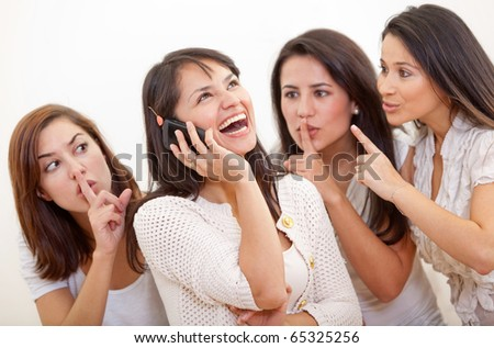 Loud woman on the phone and other girls asking her to lower her voice - stock photo