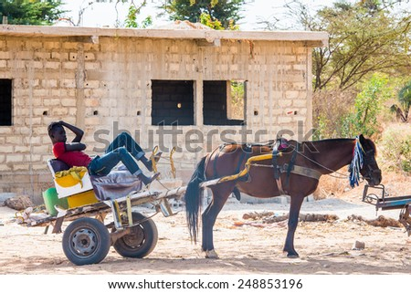 LOUGA, SENEGAL - MAR 15, 2013: Unidentified Senegalese man sits in a horse carriage. People in Senegal suffer of poverty due to the unstable economic situation - stock photo