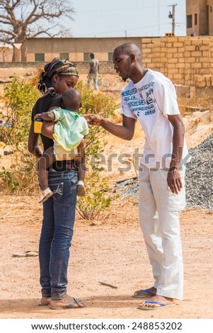 LOUGA, SENEGAL - MAR 15, 2013: Unidentified Senegalese man talks to the woman with her baby. People in Senegal suffer of poverty due to the unstable economic situation - stock photo