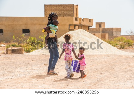 LOUGA, SENEGAL - MAR 15, 2013: Unidentified Senegalese mother and her children. Children in Senegal suffer of poverty due to the unstable economic situation - stock photo