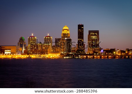 Louisville, Kentucky skyline and Ohio River at dusk - stock photo