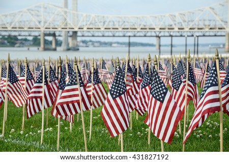 Louisville, KY, USA - May 29, 2016: American flags displayed at Waterfront Park in recognition of Memorial Day, with Ohio River bridges in background.