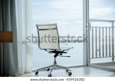 Lounge chair against huge window with seascape view - stock photo