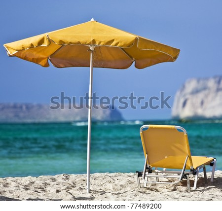 Lounge chair and umbrella on the beach - stock photo