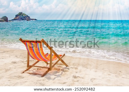 Lounge chair on the bay beach with rocks on the background - stock photo