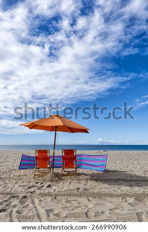 Lounge Chairs and Umbrella at the Beach - stock photo
