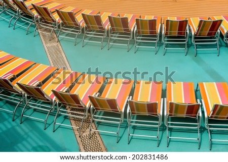 lounge chairs arranged on pool deck of cruise ship - stock photo