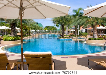 Lounge chairs by poolside in Thailand . - stock photo