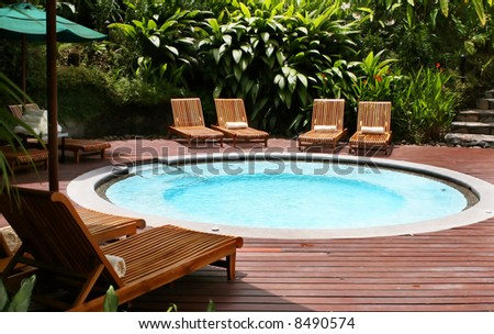 Lounge chairs surround a giant hot tub at this elegant five star resort - stock photo