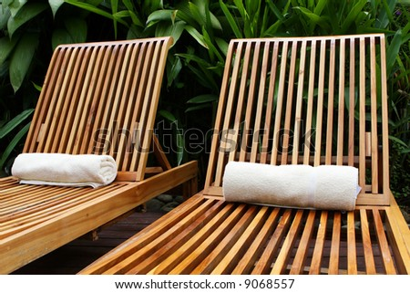 Lounge chairs surround a pool at a five star resort - stock photo