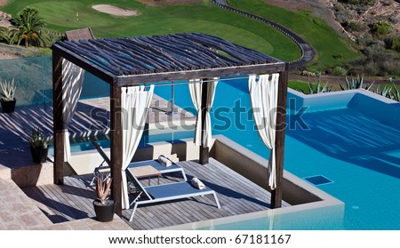 Lounge chairs under wood near the blue pool - stock photo