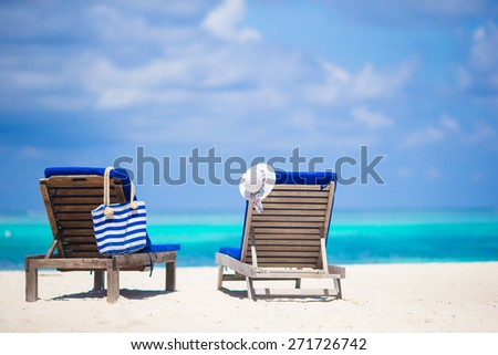 Lounge chairs with bag and hat on tropical beach at Maldives - stock photo
