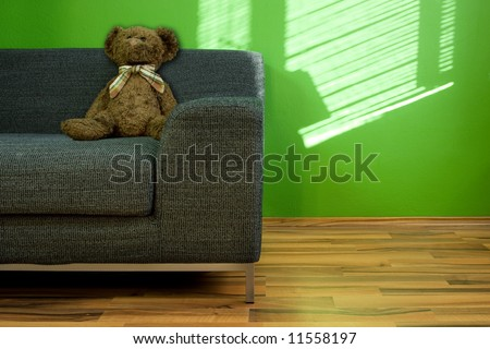 Lounge green room with couch and Teddy bear - stock photo