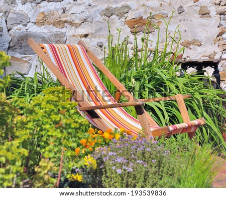 lounger among plants within a country garden - stock photo
